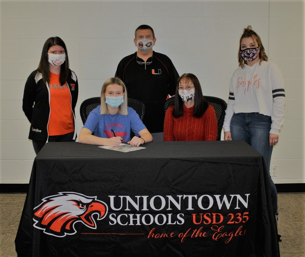 Picture of Paige Mason signing a letter of intent to cheer in college, and including her cheer coaches and her mother, and HS Athletic Director