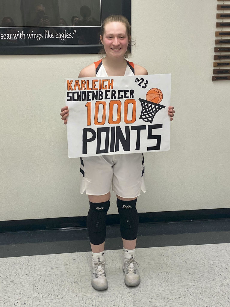 Picture of Karleigh Schoenberger with a sign reading 1,000 career points.