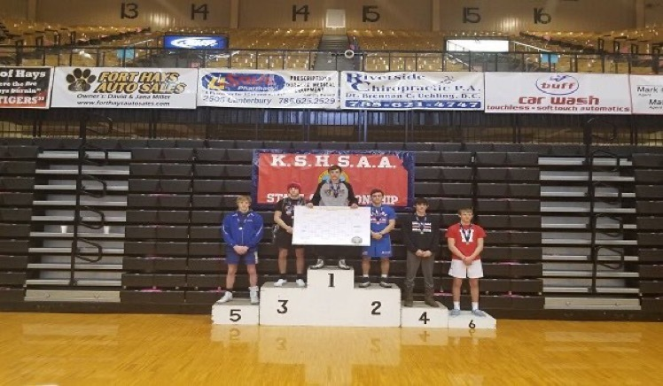 Picture of Bryce Eck on the medal stand after winning State Championship match