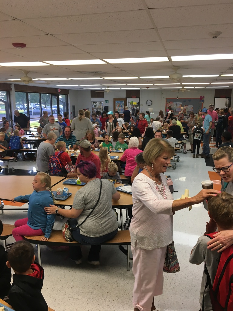 Students eating breakfast with adults