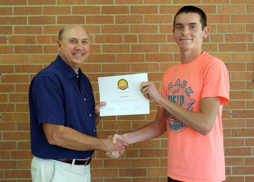 Mr. Reith presents Luke George with a certificate for being honored as a Kansas Honor Scholar.