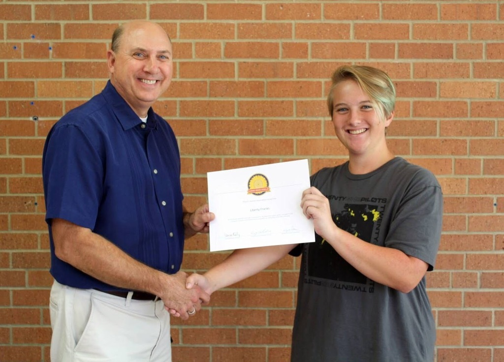 Mr. Reith presents Liberty Franks with a certificate for being honored as a Kansas Honor Scholar.