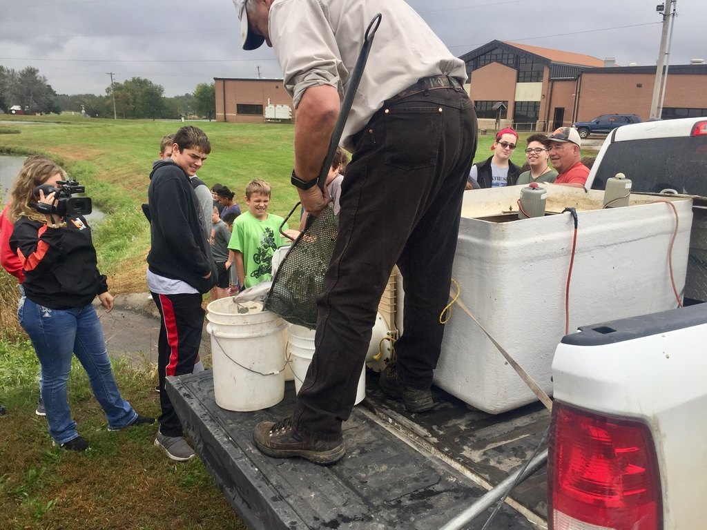 Don George transferring fish to buckets before being placed into the pond beside Uniontown JH/HS.