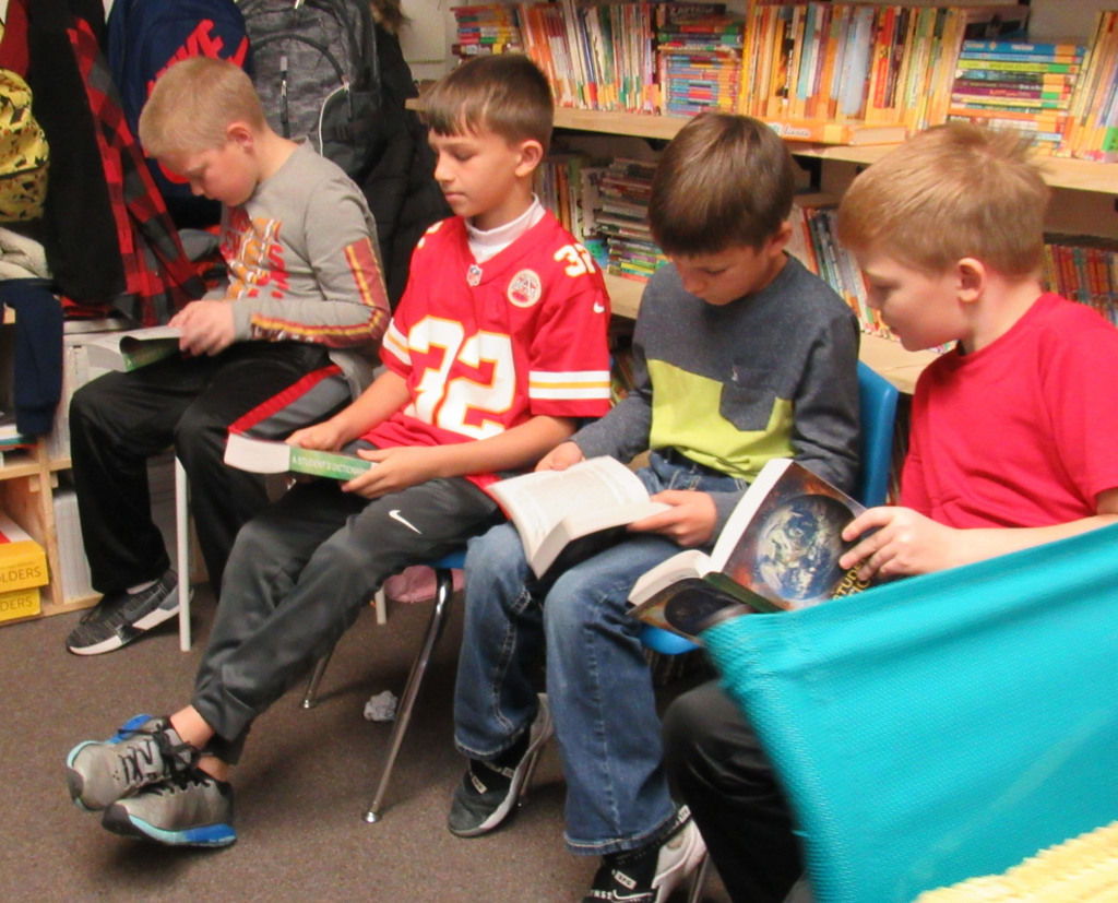 Four boys reading their dictionaries.