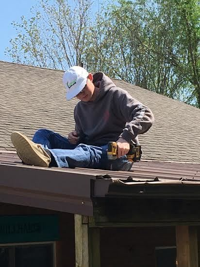 Clay Brillhart working on a metal roof