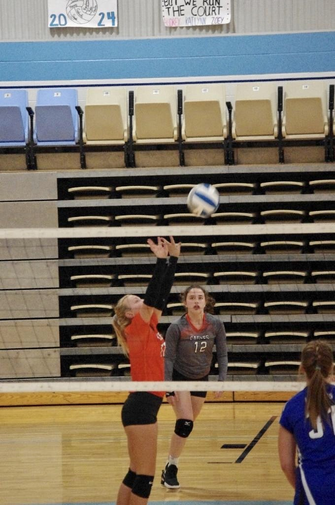 Picture of Bri Stokes setting the ball for an attack against Yates Center